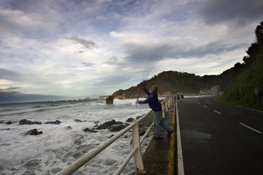 Un pescador lanza el sedal de su caÒa desde el muro de la playa de Aguilar
