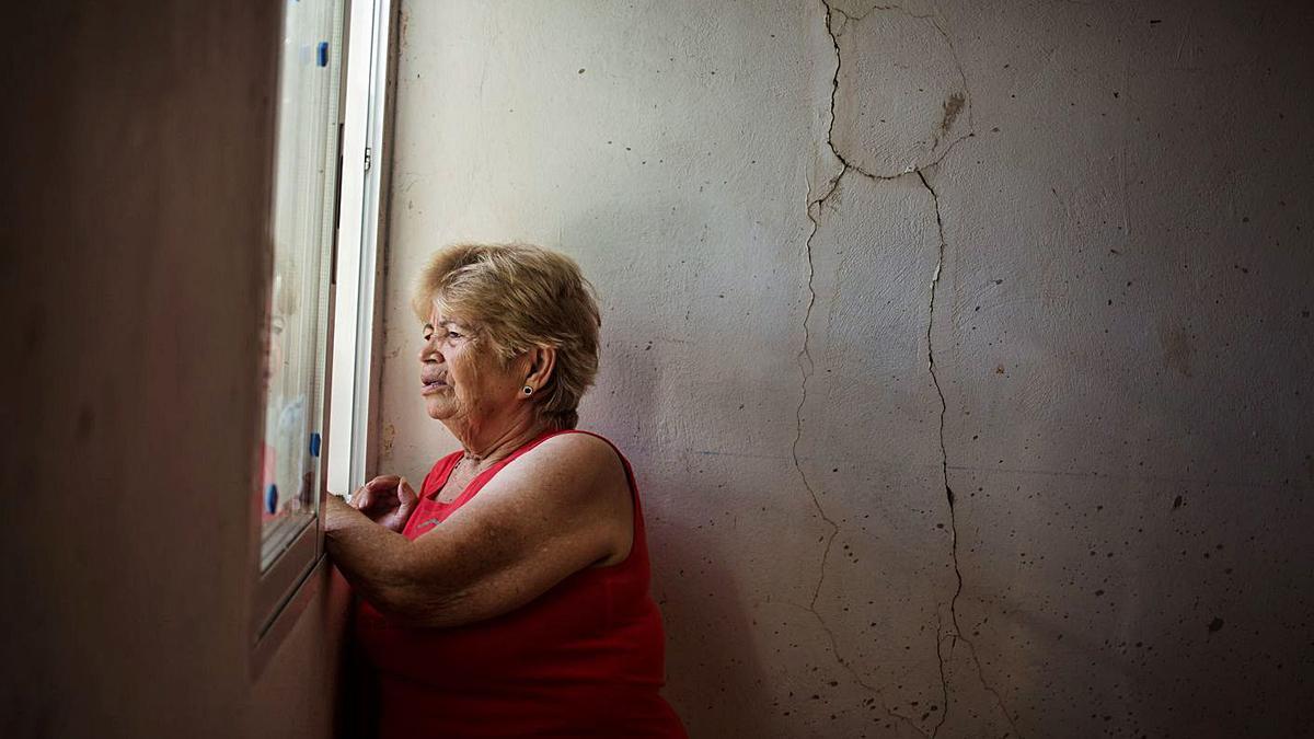 Berta Ferreiro mira por una ventana de su casa en el 102, el día que la desalojaron, en septiembre de 2014.