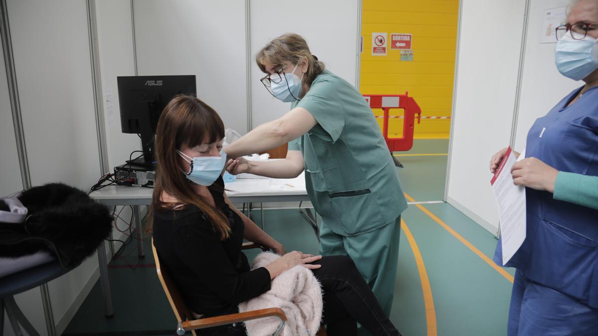 Una joven recibe una dosis de la vacuna contra el coronavirus en el Polideportivo Germans Escalas, en Palma