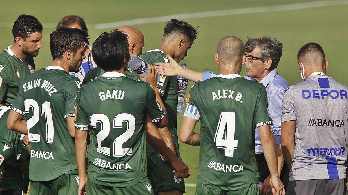 Fernando Vázquez, a la derecha, da instrucciones a sus jugadores en Tenerife durante una pausa de hidratación.