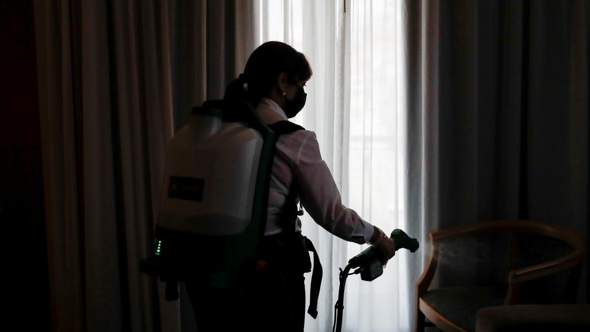 Una empleada de limpieza desinfecta una silla en un establecimiento hotelero de Lisboa.