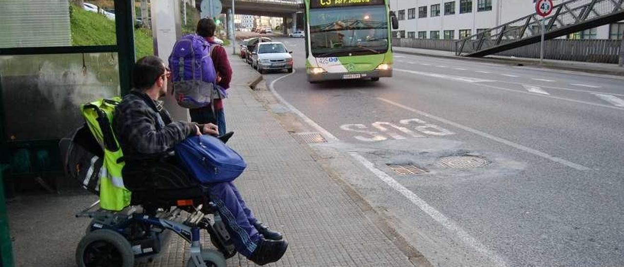 Un joven con discapacidad, en la parada del autobús. // A. Pinacho