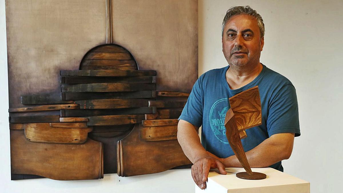 El artista Moisés Iglesias ante dos de las obras que expone en el Multiusos de A Xunqueira.     // RICARDO GROBAS