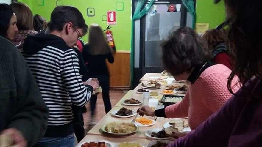 Los participantes degustan los alimentos dispuestos en la mesa.