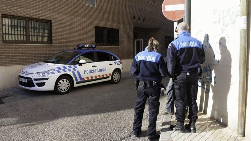 Dos agentes de la policía municipal hablan con un viandante.