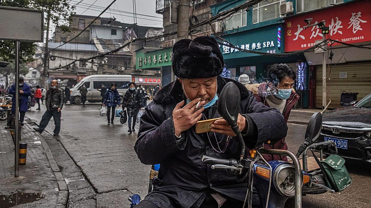 Un hombre fuma en una calle de Wuhan, ayer.   | // ROMAN PILIPEY