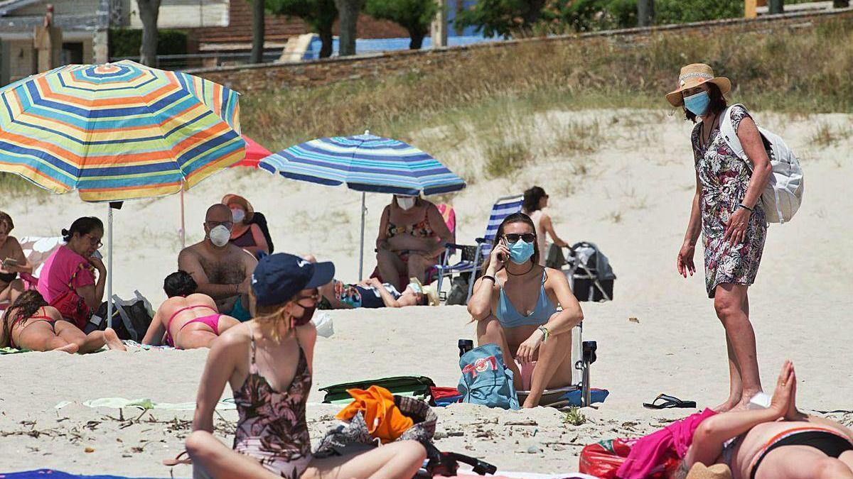 Varias personas protegidas con mascarillas toman el sol en la playa de A Rapadoira, en Foz.
