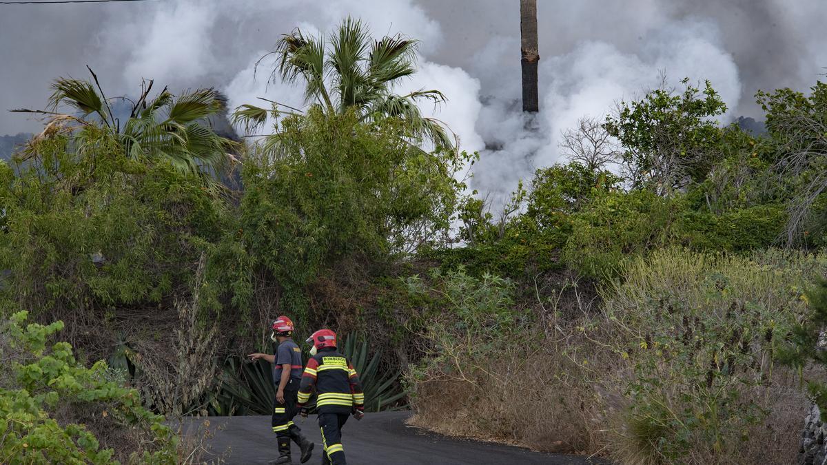 Dos bomberos trabajan en una de las zonas afectadas por la erupción del volcán, a 22 de septiembre