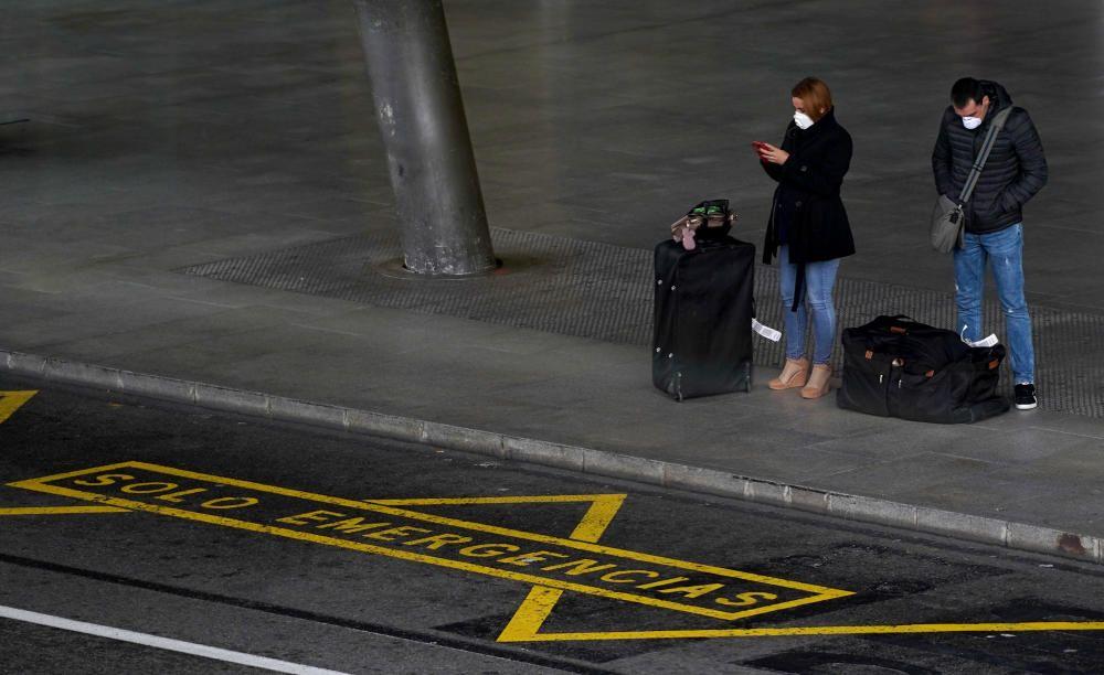 MADRID. 19.03.2020. CORONAVIRUS. Miembros de la UME limpian el aeropuerto de Barajas, terminal T4. En la imagen dos viajeros con mascarilla. FOTO: JOSE LUIS ROCA