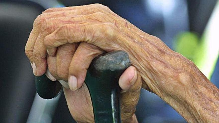 Las manos de una anciana apoyadas en el bastón.