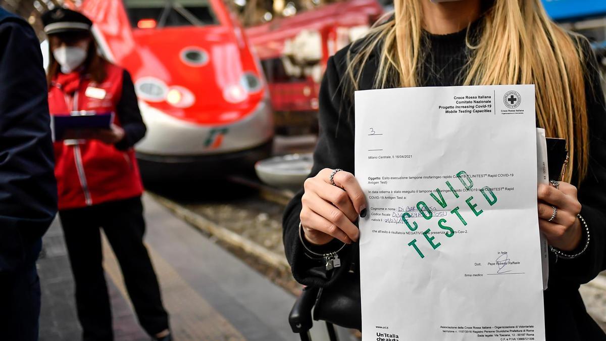 Una pasajera muestra su prueba negativa de coronavirus para poder acceder a un tren en Milán.