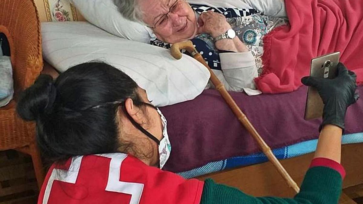 Voluntarios de Cruz Roja prestan auxilio a una anciana y participan en una campaña de recogida de material escolar. | | E.D.