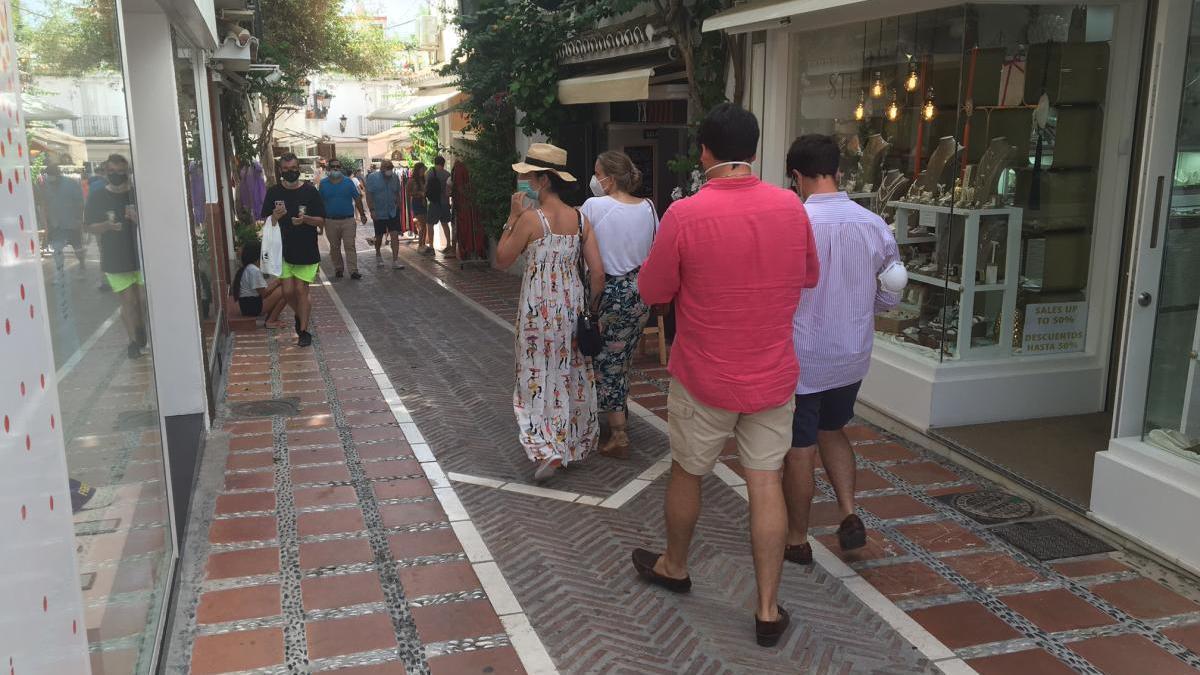 Vecinos pasean por una calle comercial del centro urbano de Marbella.