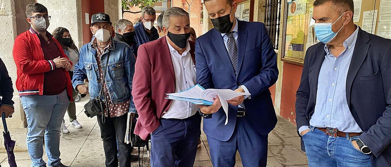 Aníbal Vázquez e Iván de Santiago observan el recurso junto a Mino García y otros simpatizantes del partido, ayer, en el acceso al Ayuntamiento de Mieres. | Vivas