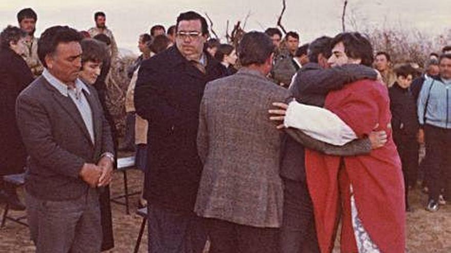 El capellán abraza a familiares de las víctimas en la misa realizada tras el accidente junto al río.