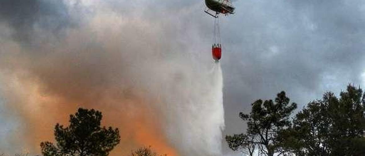 Un helicóptero participa en la extinción de un incendio el pasado mes de mayo en Lalín. // J. E.