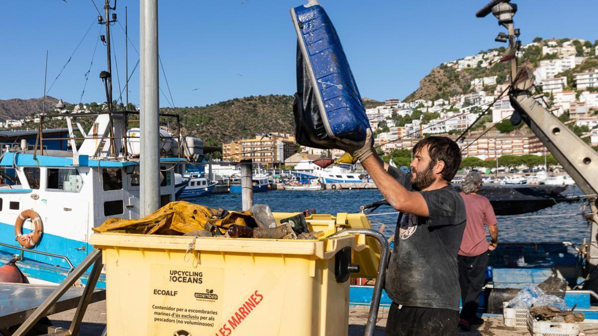 Un pescador buidant un cubell ple de residus que han capturat mentre pescaven en el Port de Roses