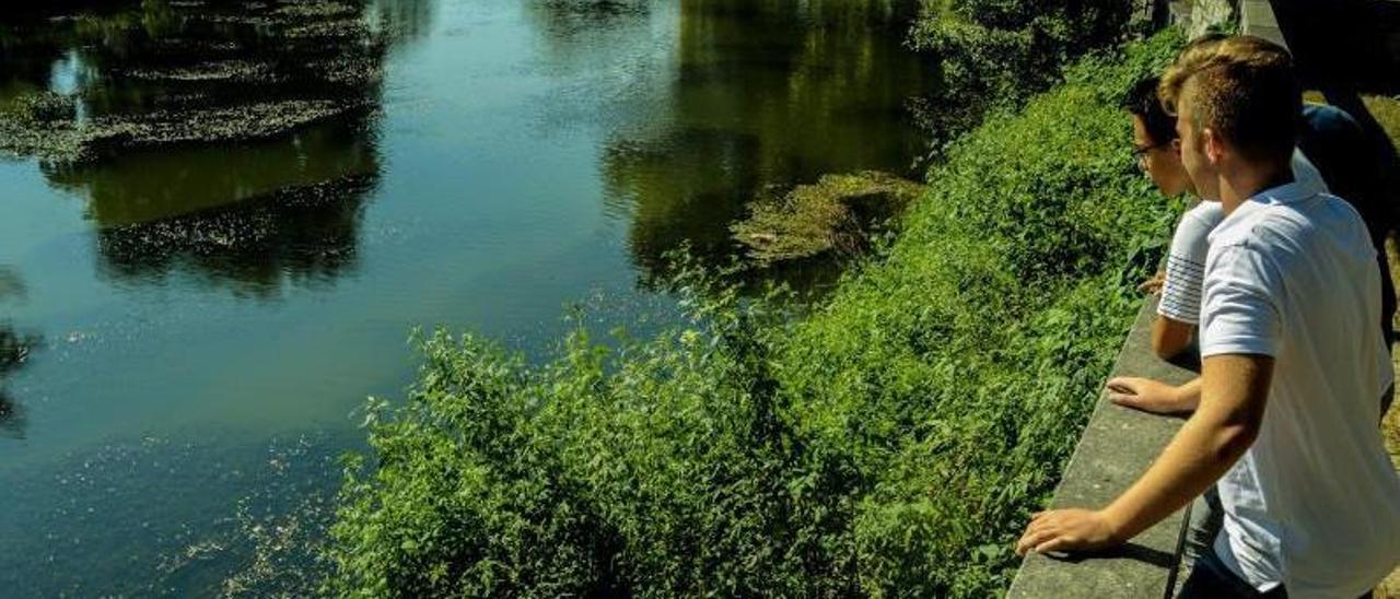Dos jóvenes observan las aguas del embalse  de Caldas afectado por cianobacterias.