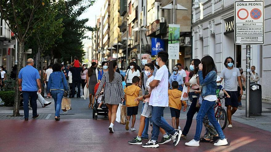 Gente paseando con mascarillas por el cruce, pintado de rojo en la anterior actuación. |   // GUSTAVO SANTOS