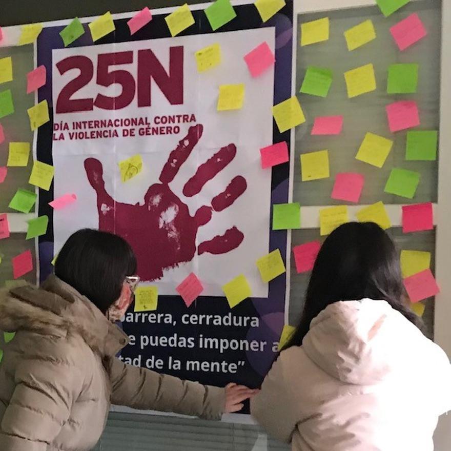Dos personas cuelgan mensajes en el mural del 25-N en el instituto de Villalpando.