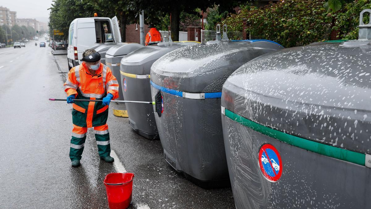 Un operario de Emulsa limpia contenedores de reciclaje
