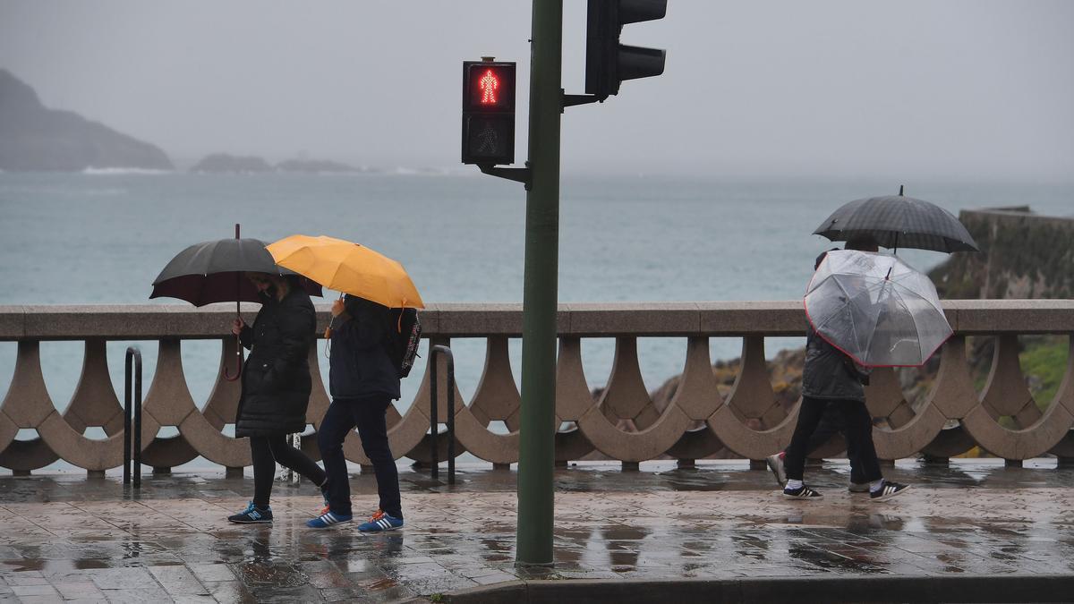 Gente protegiéndose de la lluvia en el paseo marítimo de A Coruña.