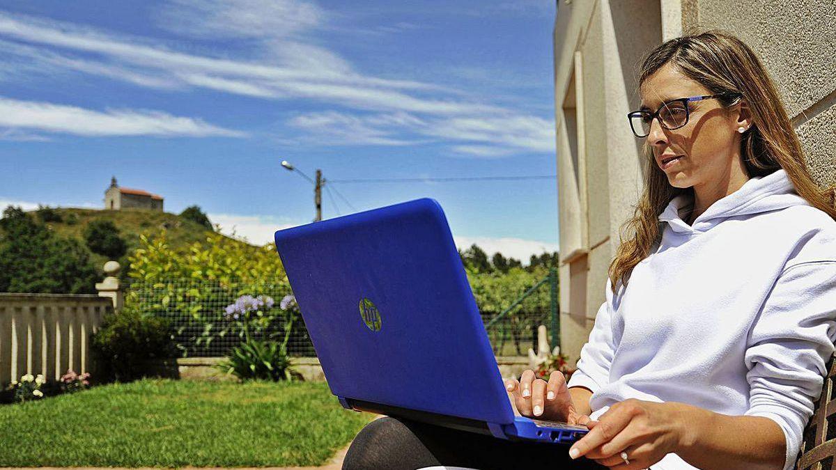 Una mujer posa con su ordenador.