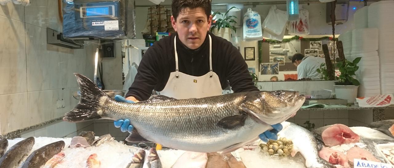 El pescadero Samuel Guillén muestra una lubina de diez kilos