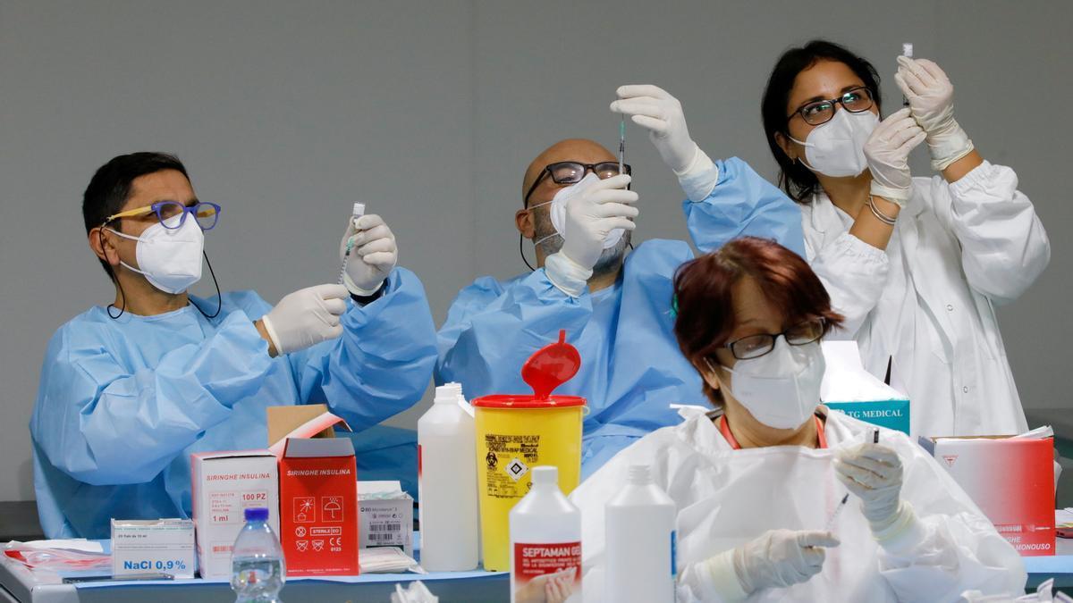Trabajadores sanitarios preparan dosis de la vacuna COVID-19 de Pfizer-BioNTech en un centro de vacunación contra el coronavirus.