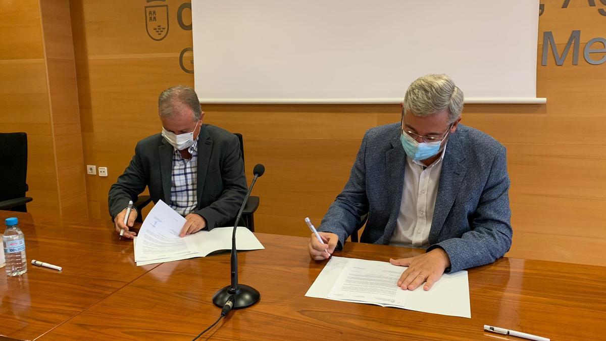 Julián Díaz García y Víctor Manuel Martínez, durante la firma.