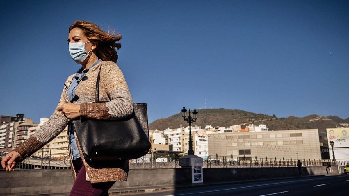 Una mujer transita por una acera de la capital tinerfeña.