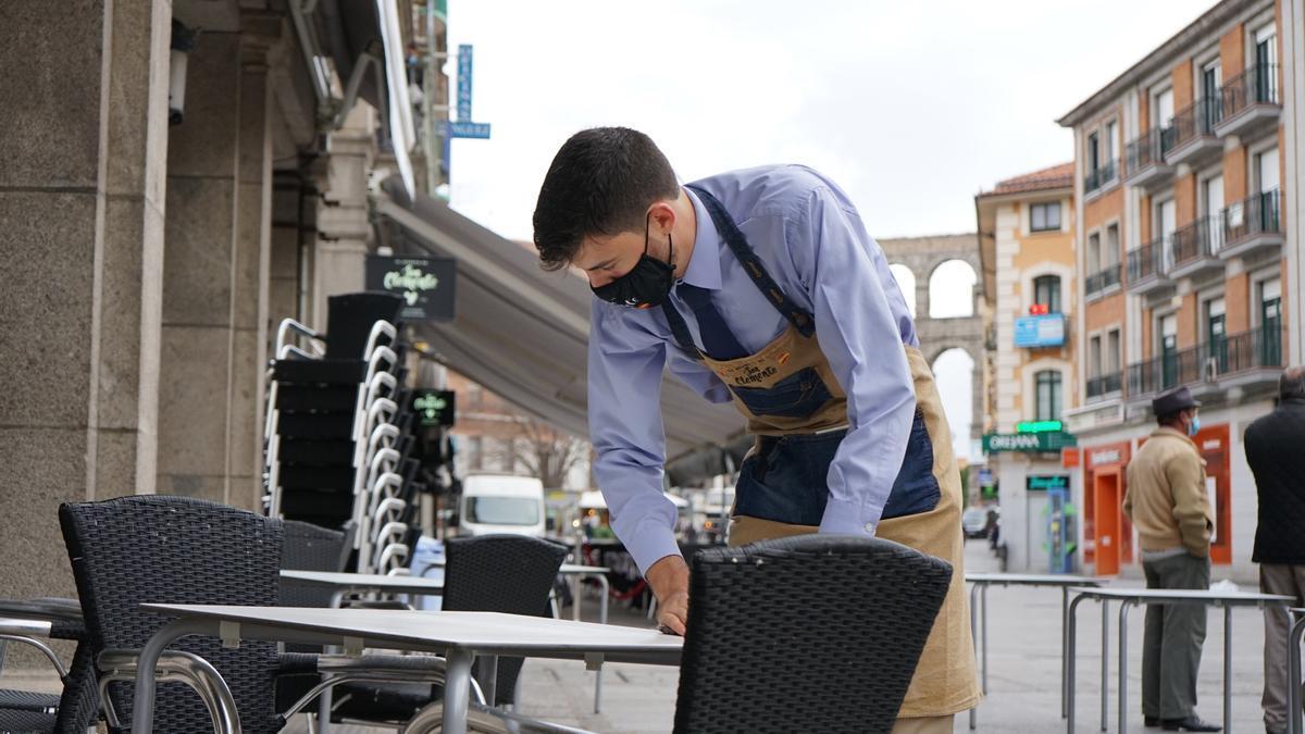 Un camarero prepara una terraza en Segovia.