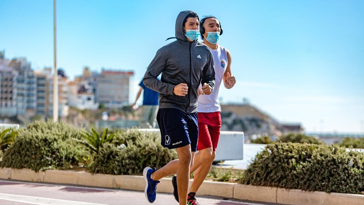 Dos corredores con mascarilla (mal puesta) en Benidorm