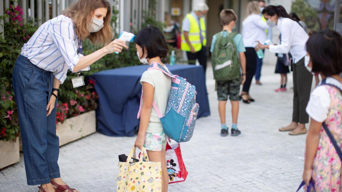 Una niña entra a un colegio en Barcelona.
