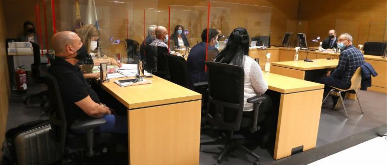 De espaldas los tres acusados junto a sus letrados durante el juicio en su contra.