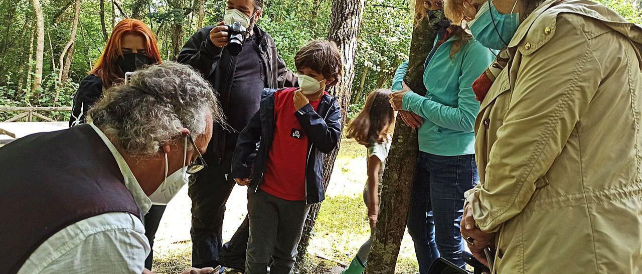 El artesano Óscar Fandos, muestra cómo talla el azabache. A la derecha, la arqueóloga Andrea Menéndez diserta sobre la extracción minera delante de una bocamina.   S. Arias
