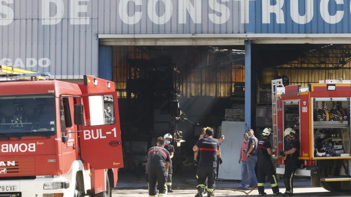 Los bomberos continúan las labores tras extinguir el incendio en una nave de la carretera de Trassierra.
