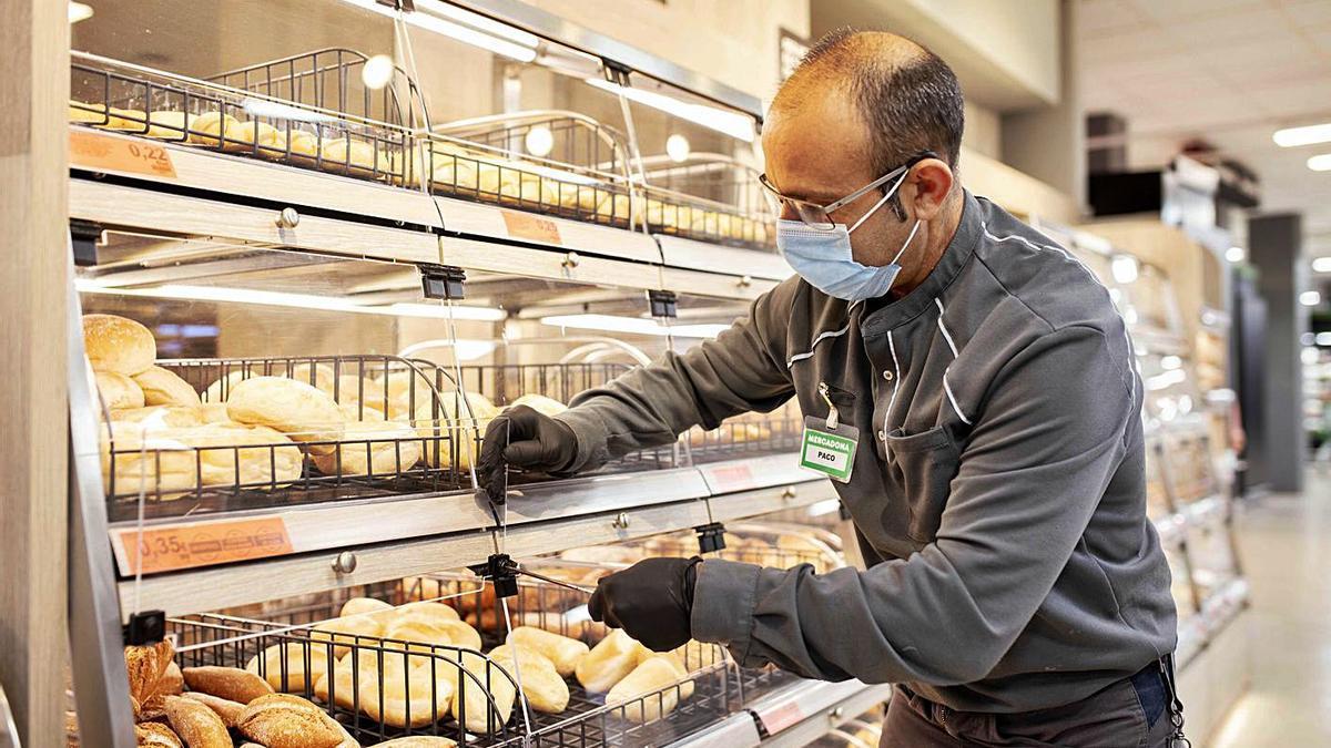 Un empleado de mantenimiento repara una vitrina en la zona de la panadería.