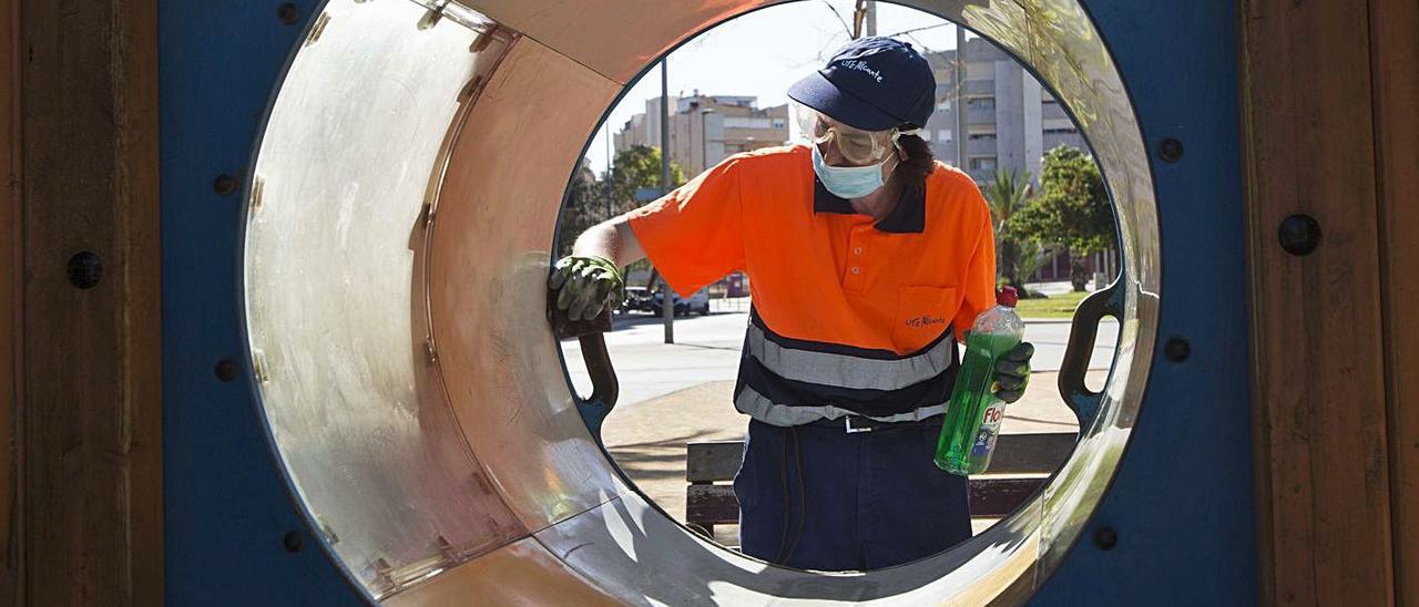 Un operario de la UTE limpia juegos infantiles en un parque de la ciudad de Alicante.