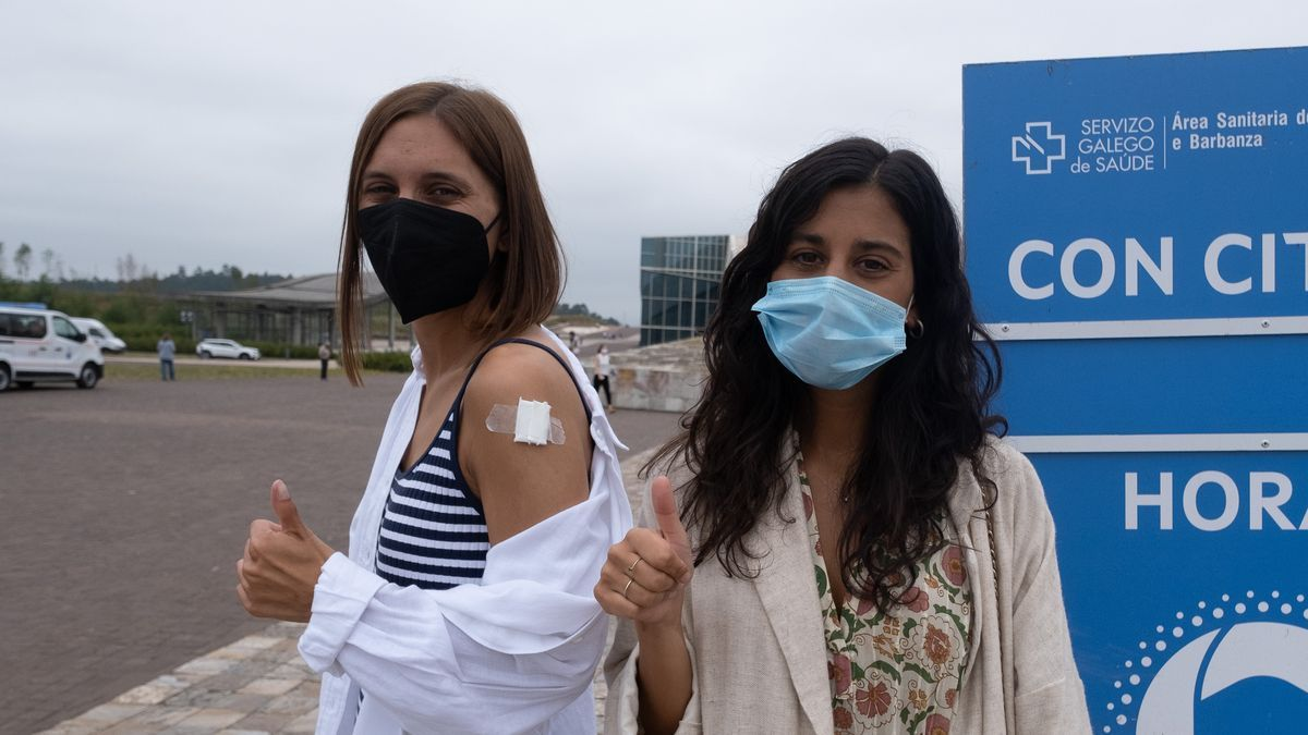Two young people greet after being vaccinated against Covid-19.