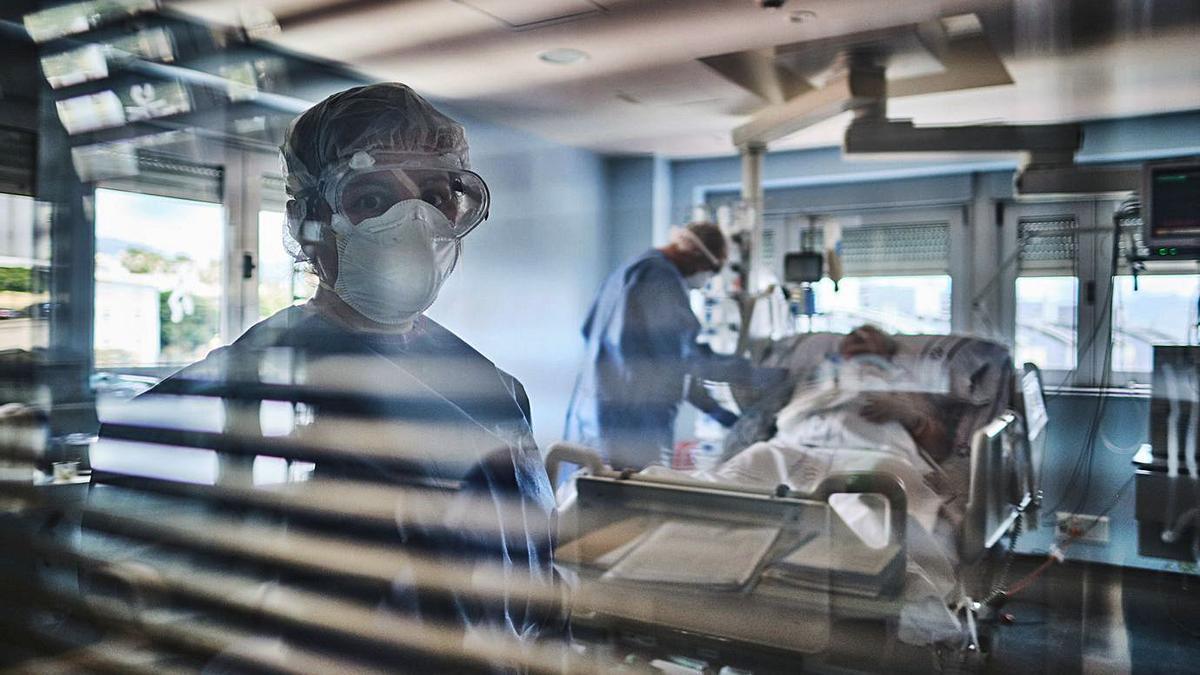 Una sanitaria tras el cristal de una sala de hospitalización de UCI para pacientes Covid-19 | | ANDRÉS GUTIÉRREZ