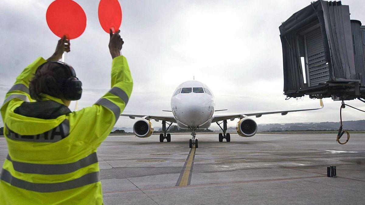 Un técnico del aeropuerto de Alvedro guía en la pista a un avión de Vueling.
