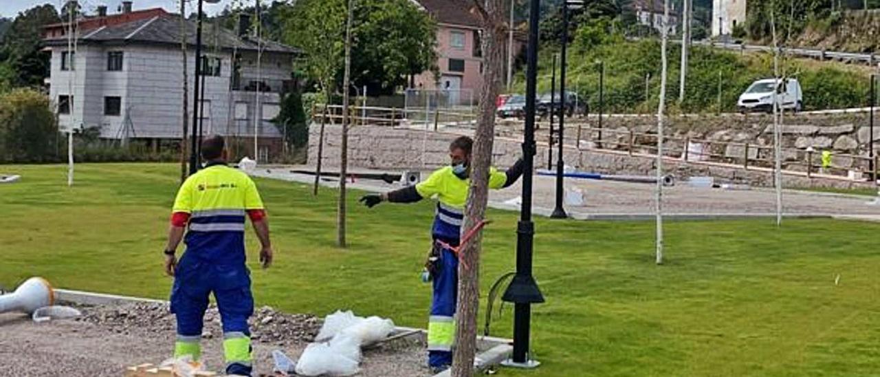 Unos operarios trabajan en el parque de Santo Estevo de Negros sobre el falso túnel del AVE. |   // C.R.