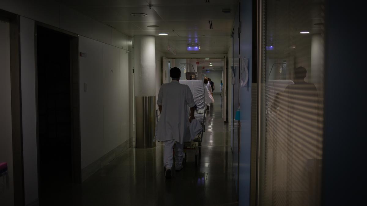 Profesional sanitario traslada una cama móvil en una Unidad de Cuidados Intensivos.