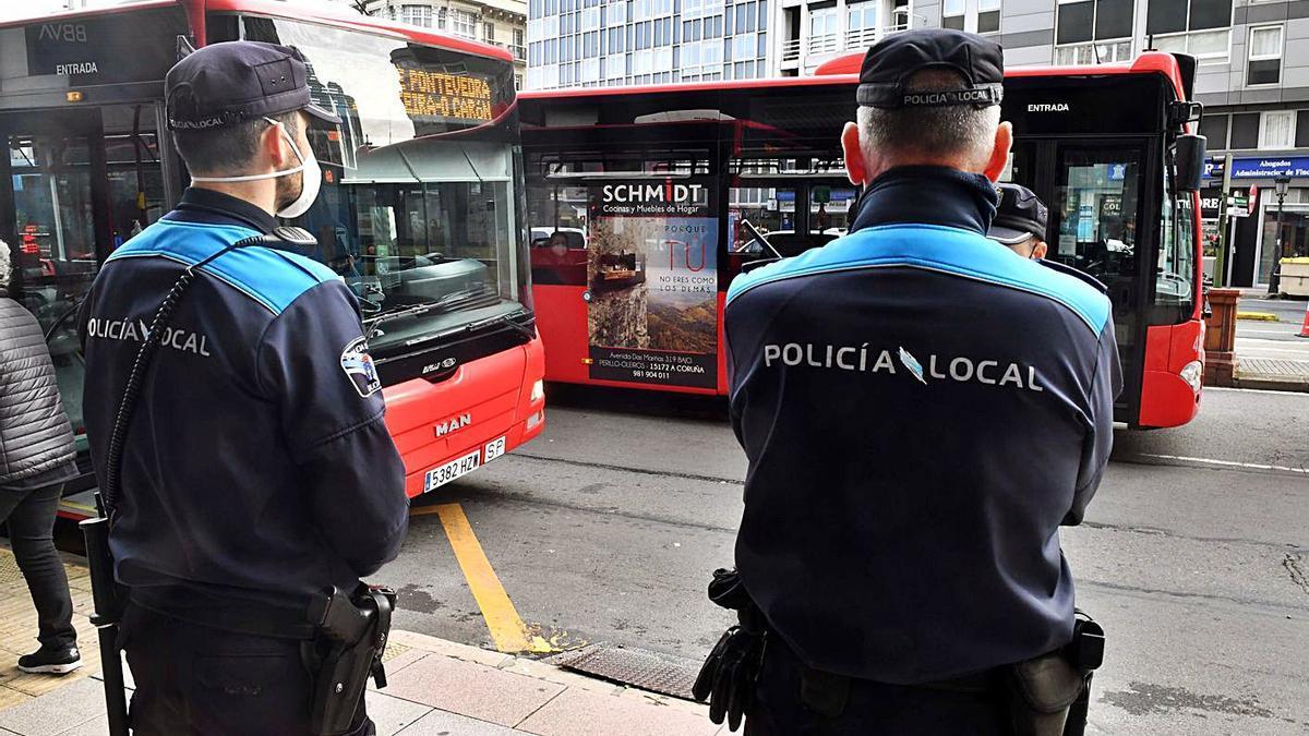Dos policías vigilan el cumplimiento de las normas sobre contagios en la plaza de Pontevedra.     // VÍCTOR ECHAVE
