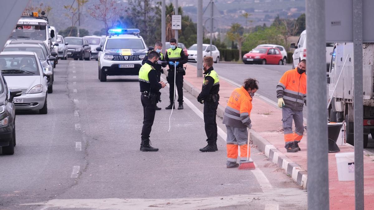 Los agentes de la Policía Local realizando el atestado y el personal de limpieza despejando la calzada.