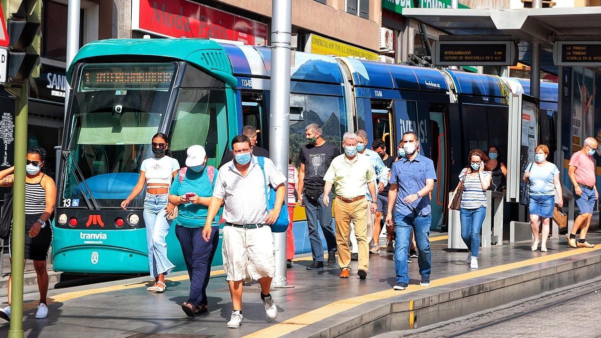 Varias personas con mascarilla salen del tranvía en la parada de Guimerá.