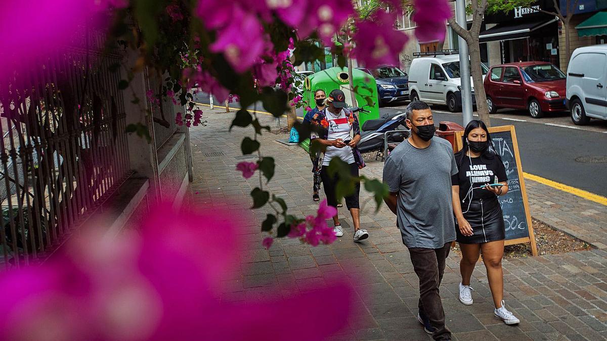 Un grupo de jóvenes pasea con mascarilla por el centro de Santa Cruz.