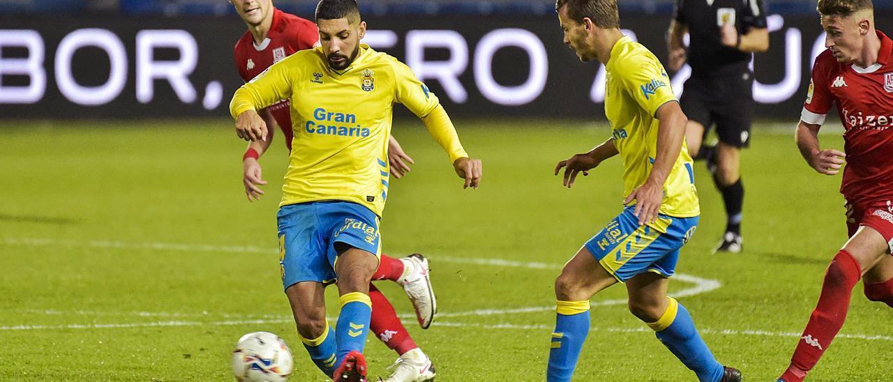 Álex Suárez golpea el balón ante la presencia del también amarillo Eric Curbelo en el partido entre la UD y el Alcorcón, en diciembre de 2020.
