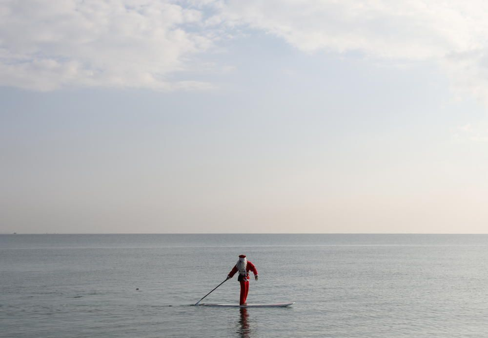A man dressed as Santa Claus paddles on a SUP ...